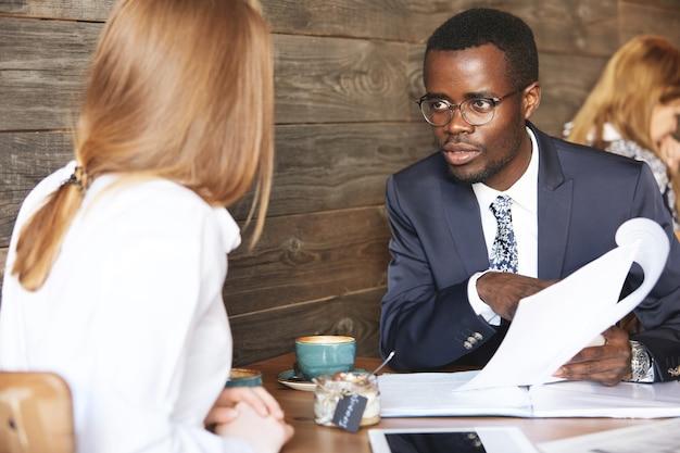Afrikaanse baas voert een interview met roodharige blanke vrouw