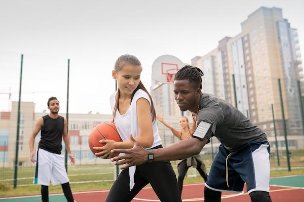 Afrikaanse basketballer die zijn hand door de bal houdt die door vrouwelijke speler wordt vastgehouden om haar niet tijdens het spel naar de mand te laten gooien