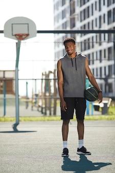 Afrikaanse basketbalspeler die bij camera glimlacht
