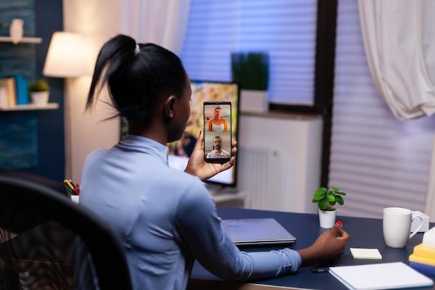 Afrikaanse bedrijfsadviseur die 's avonds laat met klanten praat vanuit het kantoor aan huis drukke werknemer die moderne technologienetwerk draadloos gebruikt en overuren maakt voor zijn werk.