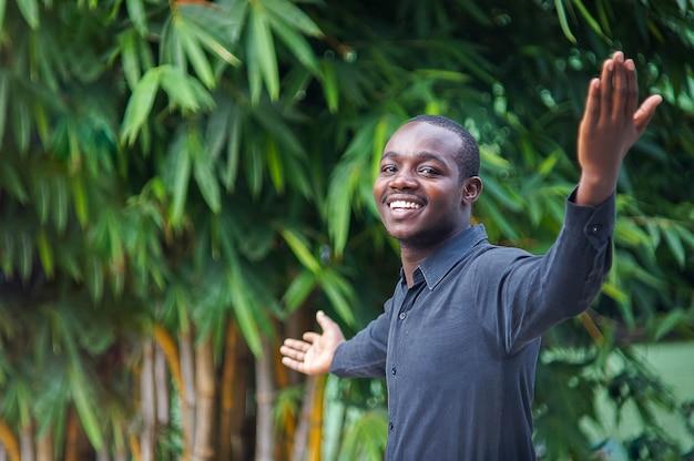 Afrikaanse bedrijfsmens die en in groene aard kijkt glimlacht.