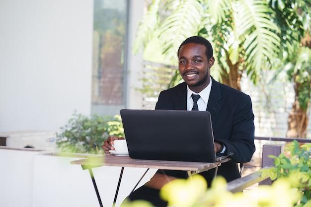 Afrikaanse bedrijfsmens die labtop en het drinken koffie speelt.