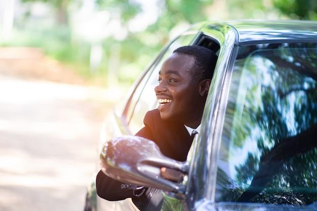 Afrikaanse bedrijfsmens die terwijl het zitten in een auto glimlacht