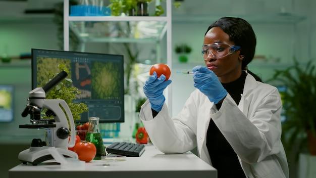 Afrikaanse biochemicus met medische handschoenen die biologische tomaat injecteert met pesticiden