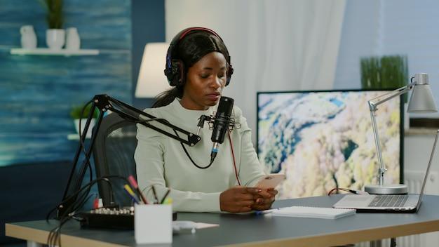 Afrikaanse bloggervrouw die berichten leest op smartphone die video opneemt voor haar blog in de thuisstudio. on-air online productie internet uitzending show host streaming live content voor sociale media