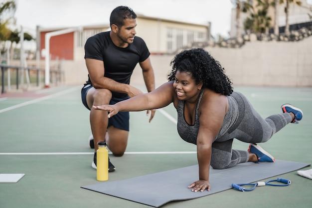 Afrikaanse bochtige vrouw en personal trainer doen pilates-trainingssessie buiten - hoofdfocus op meisjesgezicht