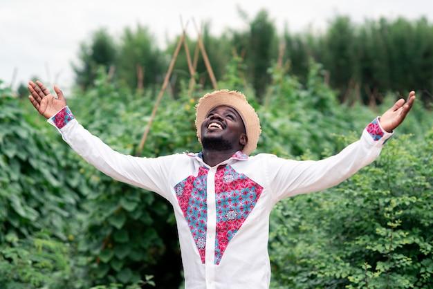 Afrikaanse boer man permanent in de biologische boerderij met het dragen van inheemse kleding. landbouw of teeltconcept