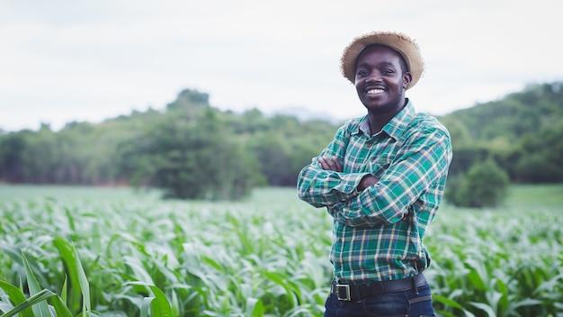 Afrikaanse boer man permanent op biologische boerderij met glimlach en gelukkig. landbouw of teelt concept