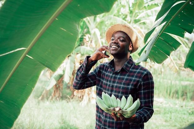 Afrikaanse boer man praten over smartphone en banaan op biologische boerderij met glimlach en gelukkig. landbouw of teelt concept