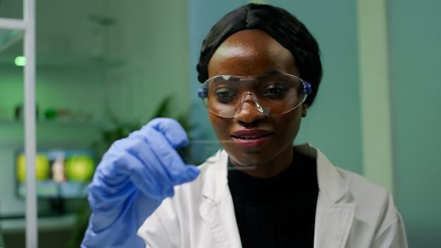 Afrikaanse botanicusvrouw die genetisch testmonster bekijkt voor biologisch experiment