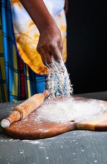 Afrikaanse chef-kok die met bloem werkt