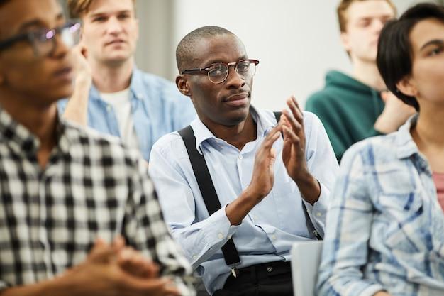 Afrikaanse conferentiedeelnemer applaudisseert voor spreker