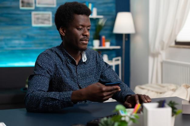Afrikaanse consument die online winkelt in de uitverkoop winkel betalende bestelling met creditcard. student zit aan bureau in woonkamer en doet online betaling met elektronische portemonnee met behulp van computer
