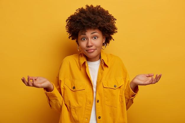 Afrikaanse dame haalt haar schouders op en spreekt onzekerheid uit, neemt een beslissing, draagt modieuze kleding, spreidt haar handpalmen zijwaarts geïsoleerd op gele muur.