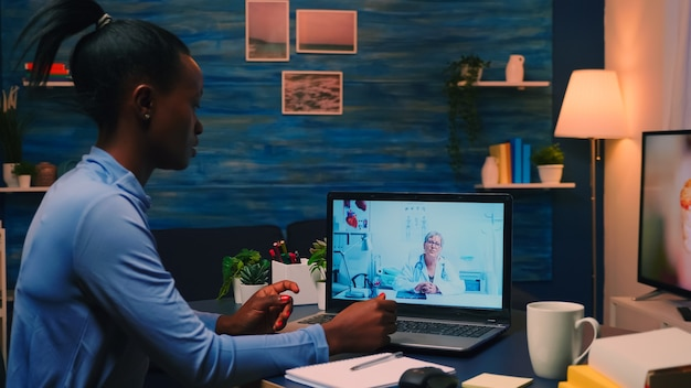 Afrikaanse dame schrijft notities tijdens online medisch consult, luisterende vrouw arts zit achter laptop in de woonkamer. vrouw bespreken tijdens videoconferentie over symptomen en behandeling.
