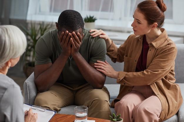 Afrikaanse depressieve man huilt terwijl ze een consult heeft samen met zijn vrouw, ze bezoeken een psycholoog