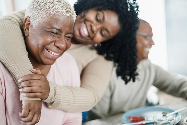 Afrikaanse dochter haar moeder knuffelen tijdens de lunch maaltijd thuis - liefde en familie concept - belangrijkste focus op senior vrouw gezicht