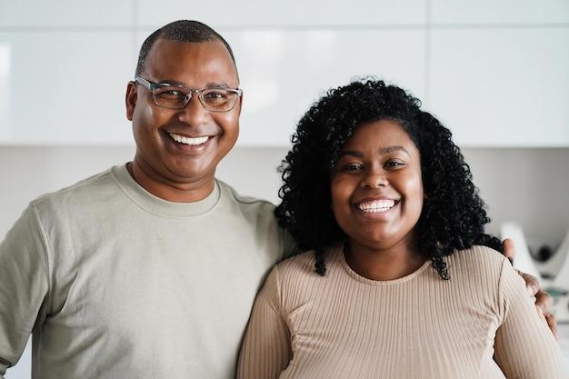 Afrikaanse dochter met teder moment met haar vader thuis