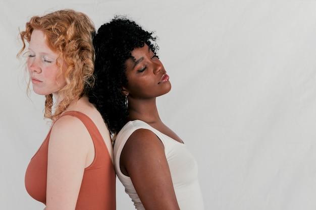 Afrikaanse en blonde jonge vrouw die het rijtjes slapen tegen grijze achtergrond bevindt zich