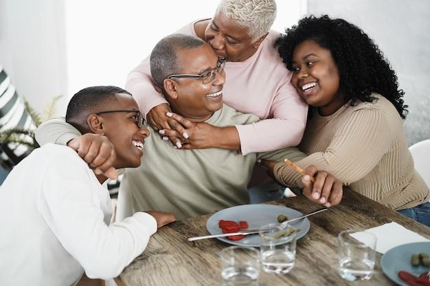Afrikaanse en gelukkige familie met teder moment eten lunch thuis