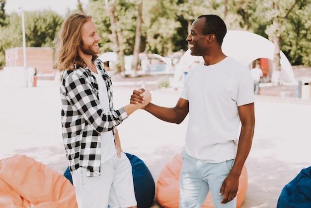 Afrikaanse en kaukasische mannen handshaking op strand