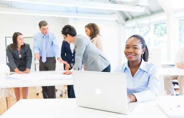 Afrikaanse etnische vrouw die bij de camera glimlachen terwijl het werken aan haar laptop met commerciële vergadering als