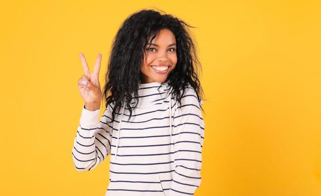 Afrikaanse etnische vrouw in wit gestreepte hoodie poseert op een gele achtergrond, toont duimen, kijkt naar de camera en glimlacht vrolijk