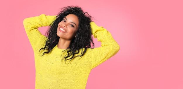 Afrikaanse etnische vrouw met gitzwart golvend haar in geel gebreid sweatshirt poseert terwijl ze naar de camera kijkt en lacht van vreugde
