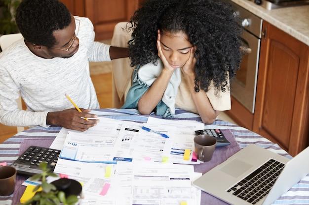 Afrikaanse familie die papierwerk samen doet. benadrukt jonge vrouw hand in hand op haar gezicht, depressief kijkend, geschokt door de hoeveelheid gezinsuitgaven, haar ondersteunende echtgenoot die haar probeert te kalmeren