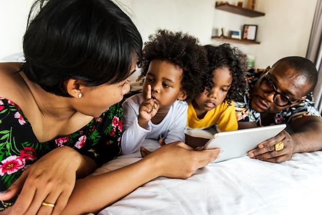 Afrikaanse familie op bed met behulp van een tablet