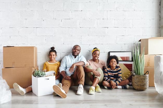 Afrikaanse familie van vader, moeder en twee kinderen in vrijetijdskleding zittend tegen een wit geschilderde muur op de vloer van een grote woonkamer