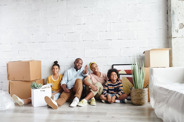 Afrikaanse familie van vader, moeder, zoontje en tienerdochter in vrijetijdskleding zittend tegen wit geschilderde muur op de vloer van de woonkamer