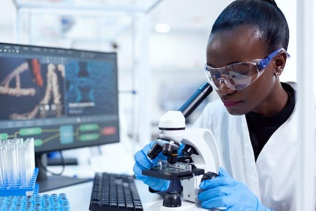 Afrikaanse farmacologieonderzoeker die chemische stof analyseert met behulp van de microscoop voor studie... zwarte gezondheidswetenschapper in biochemielaboratorium met steriele apparatuur.