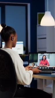 Afrikaanse freelancer die op afstand werkt en met partner praat