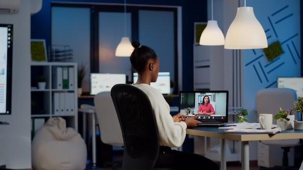 Afrikaanse freelancer werkt op afstand en bespreekt online met vrouwelijke partner