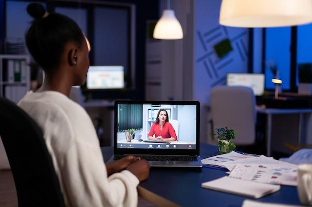 Afrikaanse freelancer werkt op afstand in gesprek met vrouwelijke partner online zittend voor laptop in start-up kantoor praten tijdens virtuele vergadering om middernacht, overuren maken