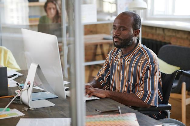 Afrikaanse gehandicapte zakenman zit op zijn werkplek en werkt op de computer op kantoor