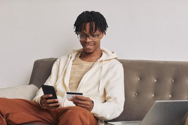 Afrikaanse gelukkig man zittend op de bank en het gebruik van zijn mobiele telefoon om rekeningen online te betalen met een creditcard