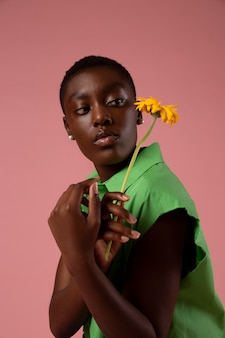 Afrikaanse genderfluïde persoon die in een groen shirt poseert green