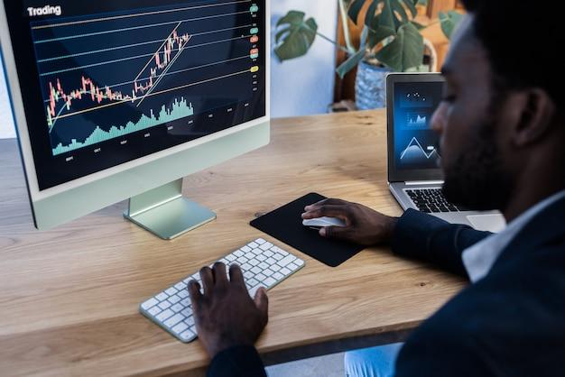 Afrikaanse handelaar die thuis aandelenmarkt bestudeert - focus op computerscherm