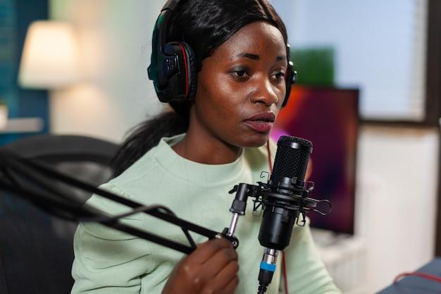 Afrikaanse influencer die inhoud opneemt met professionele microfoon in thuisstudio. sprekend tijdens livestreaming, blogger discussiërend in podcast met koptelefoon op.