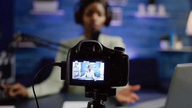 Afrikaanse influencer-opnameblog die naar professionele camera kijkt in de thuisstudio van een online talkshow