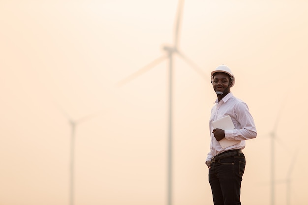 Afrikaanse ingenieur die witte bouwvakker draagt die zich met digitale tablet tegen windturbine bevindt op zonnige dag