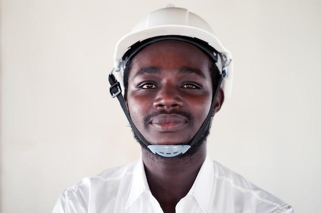 Afrikaanse ingenieursmens die witte helm met een gelukkige en koele glimlach op gezicht draagt.