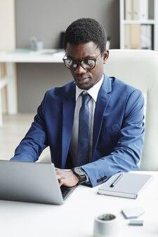 Afrikaanse jonge kantoormedewerker in pak zit op zijn werkplek te typen op de laptop die hij online op kantoor werkt