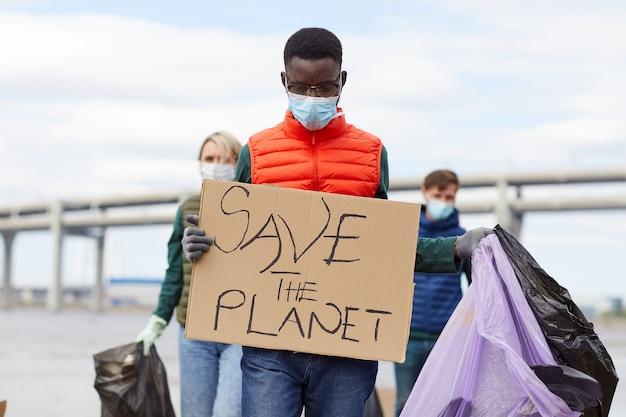 Afrikaanse jonge man in beschermend masker met plakkaat met andere vrijwilligers die op de achtergrond buitenshuis werken