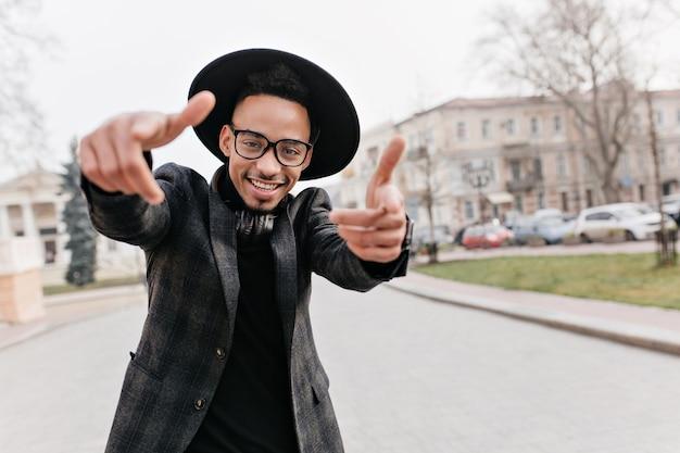 Afrikaanse jonge man in goed humeur dansen. grappige mulat kerel gek rond tijdens de vrije tijd op straat.