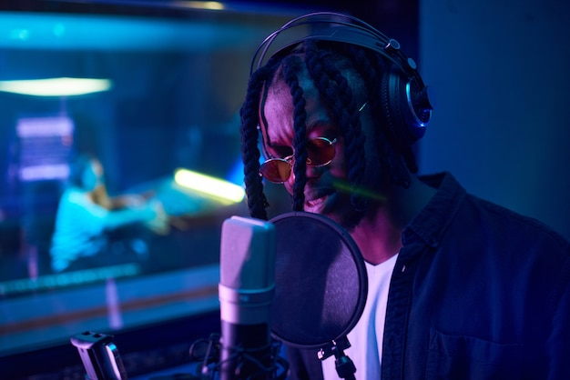Afrikaanse jonge man in zonnebril met dreadlocks die een koptelefoon draagt en zijn lied in de studio zingt