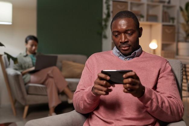 Afrikaanse jonge man zittend op een stoel en het spelen van spel op zijn mobiele telefoon met vrouw met laptop op de achtergrond