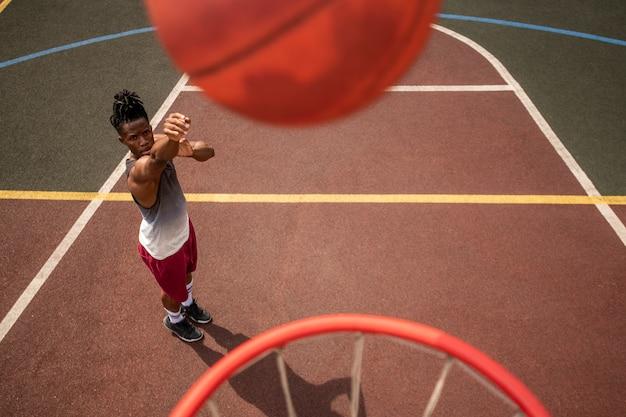Afrikaanse jonge sportman bal gooien in de mand terwijl hij tijdens de training op het veld staat